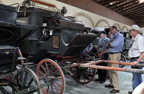 David Freedman and several members of the group discuss one of Miguel's yet-to-be-restored carriages
