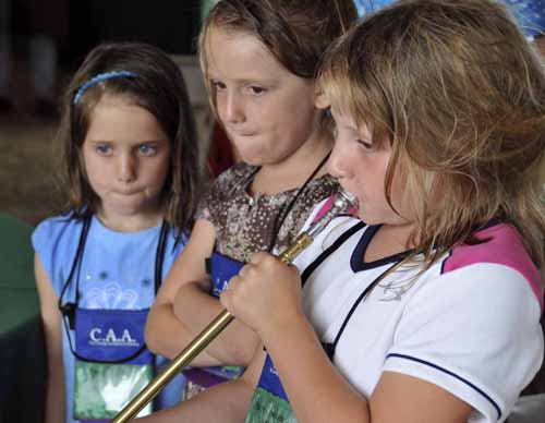 "the two girls not trying to play the horn are practising the ""pused lips"" technique they were learning for blowing a coach horn"
