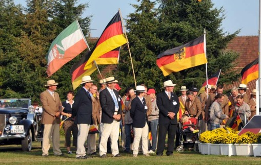 more of the German team members, grooms, families, etc. ... standing next to the podium and watching the proceedings