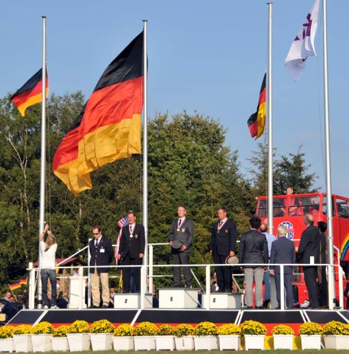 the German fans were shouting and singing in anticipation of the medal ceremony for the pairs division, which was swept by German drivers; those same fans were ecstatic with the enormous flag the organizers produced for their gold-medal winner